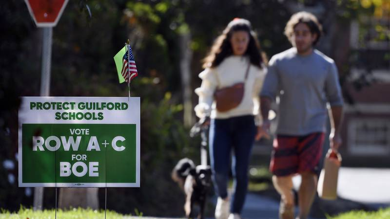 People walk near one of many signs around town centered around the upcoming Nov. 2 election and...