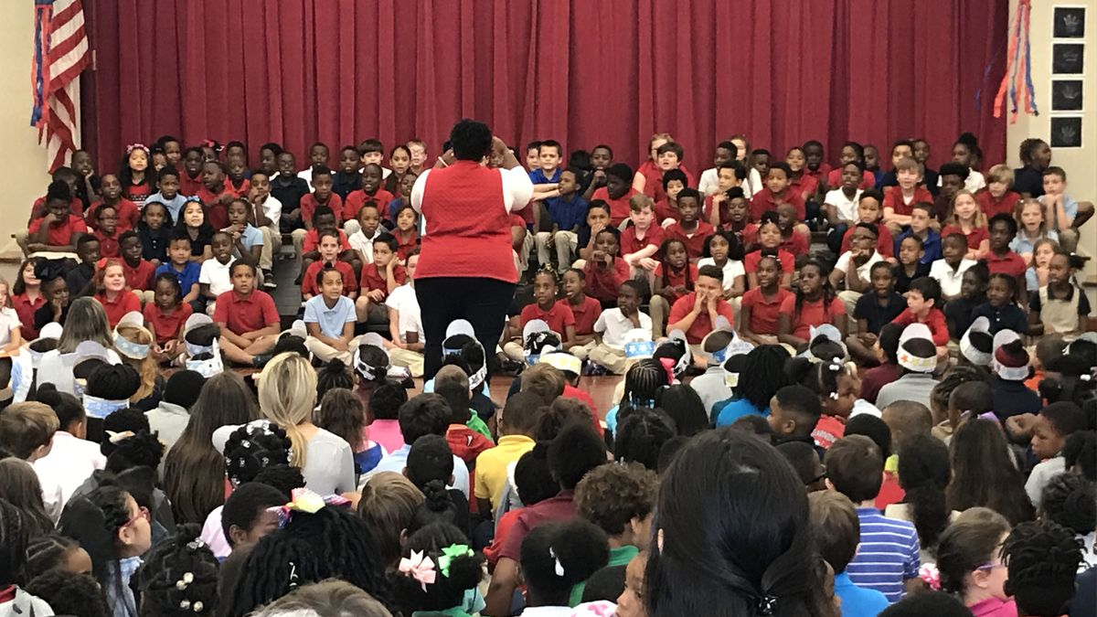 Latresha Woods directs the second graders through a performance during their Veteran's Day program.