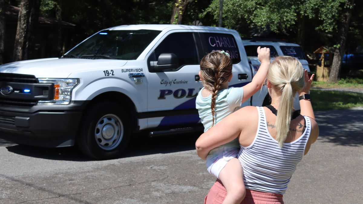 Charli Betts, 5, and her mother, Bree, wave to a passing Crestview Police pick-up which was part of a parade organized in her honor. The girl was diagnosed with a rare brain stem cancer.