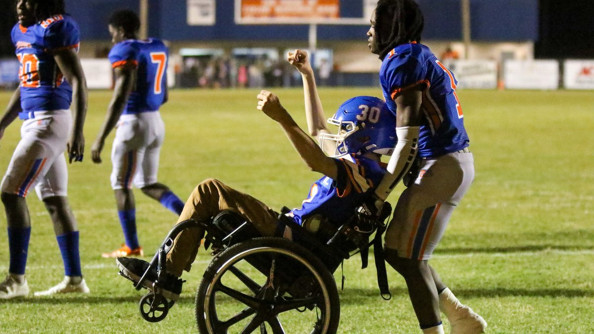 The Taylor County football team helped wheelchair-bound fan Cycless Gorlewski across the goal...