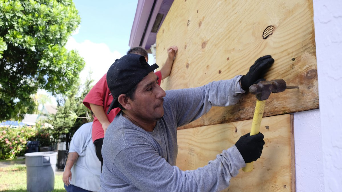 Pedro Reimundo installs wood shutters on a home in Florida City, Fla., Friday, Sept. 8, 2017....