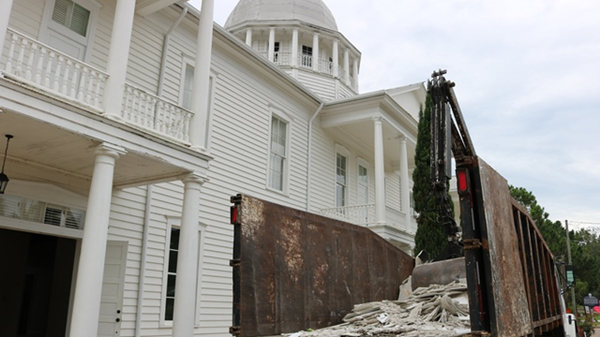 Dump truck in front of Chautauqua Hall of Brotherhood being filled with debris from walls not...