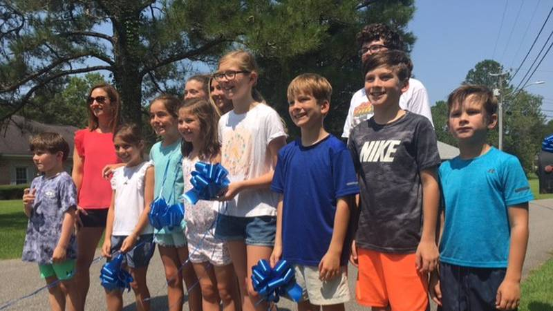 Neighborhood children volunteered their time to tie more than a hundred blue ribbons to...