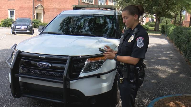 """Troy University Police Officer Rachel Farmer scrolls through the """"Omnilert"""" app."""