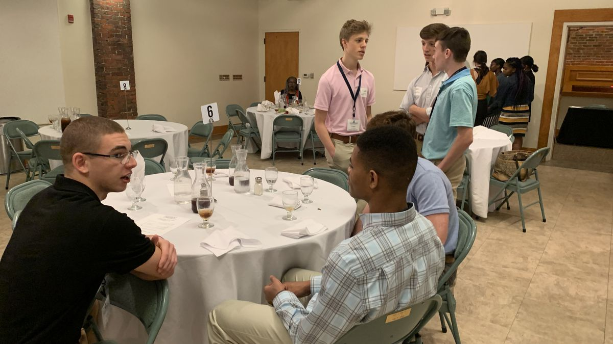 Local high school students conversing at leadership luncheon