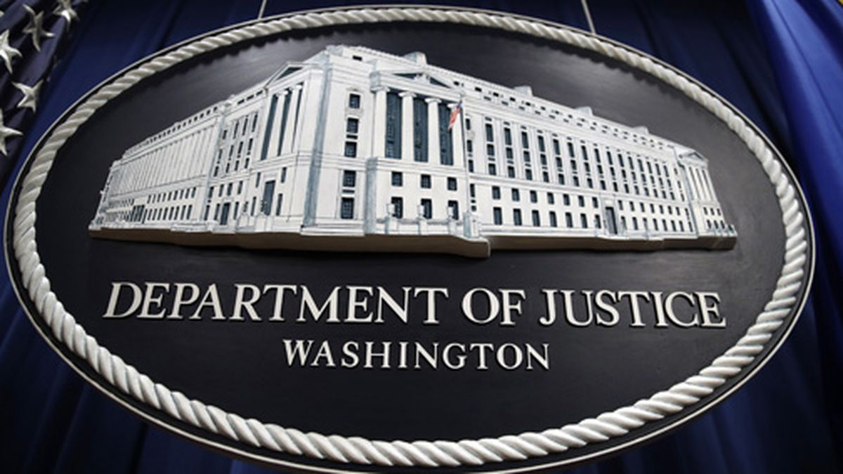 In this Thursday, April 18, 2019 file photo, a sign for the Department of Justice hangs in the press briefing room at the Justice Department, in Washington. The U.S. Justice Department is conducting an antitrust investigation of four automakers that have signed on with California in a deal to toughen tailpipe emissions standards. In July, Ford, Honda, Volkswagen and BMW reached a deal with California to abide by standards that are tougher than those preferred by the Trump administration. The standards are closely linked with fuel economy requirements. (AP Photo/Patrick Semansky, File)