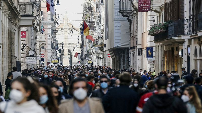 FILE - In this Saturday, Feb. 7, 2021 file photo, people crowd Via del Corso shopping street in...