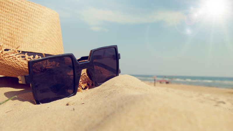 Sunglasses and hat on sand.