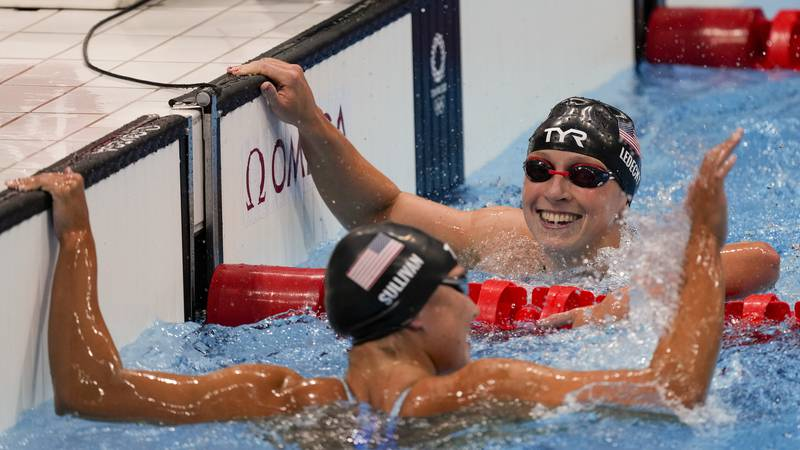 Katie Ledecky, right, of the United States, celebrates after winning the women's 1500-meters...