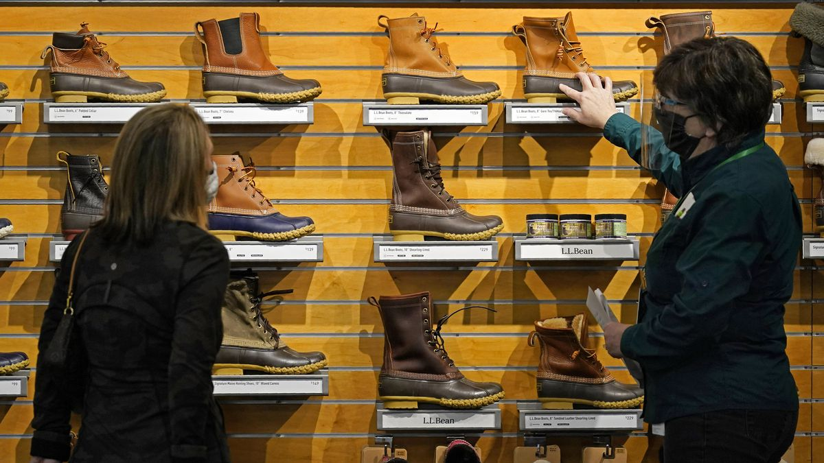 FILE - In this March 18, 2021 file photo, a salesperson helps a customer shopping for boots at...