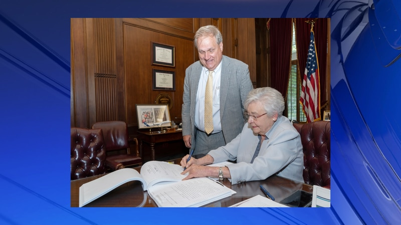 Gov. Kay Ivey signs SB46 with Senator Tim Melson