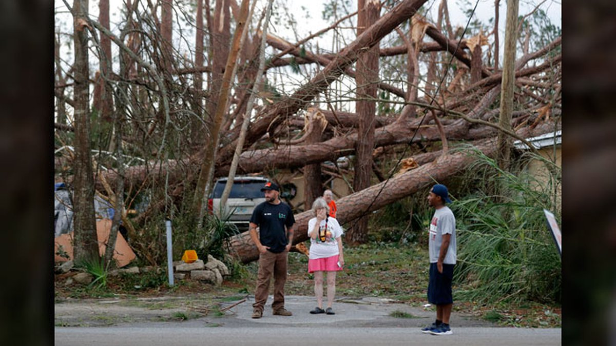 FILE PHOTO: Joyce Fox, center stands in front of her heavily damaged home in the aftermath of...