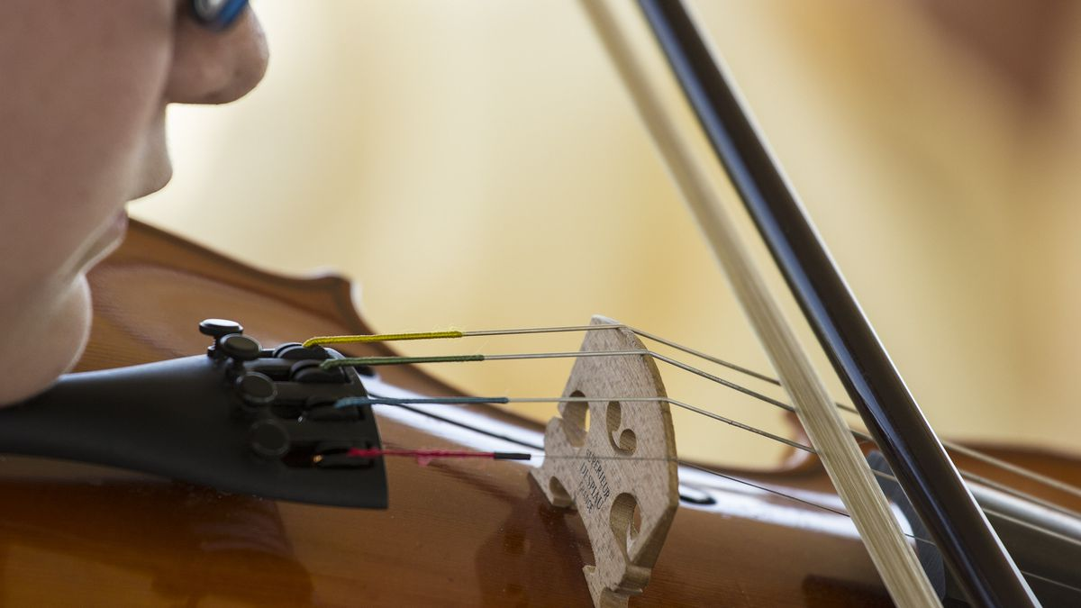 Adella Birdwell of kansas city, kansas, age 13, plays the violin in the instrument petting zoo...