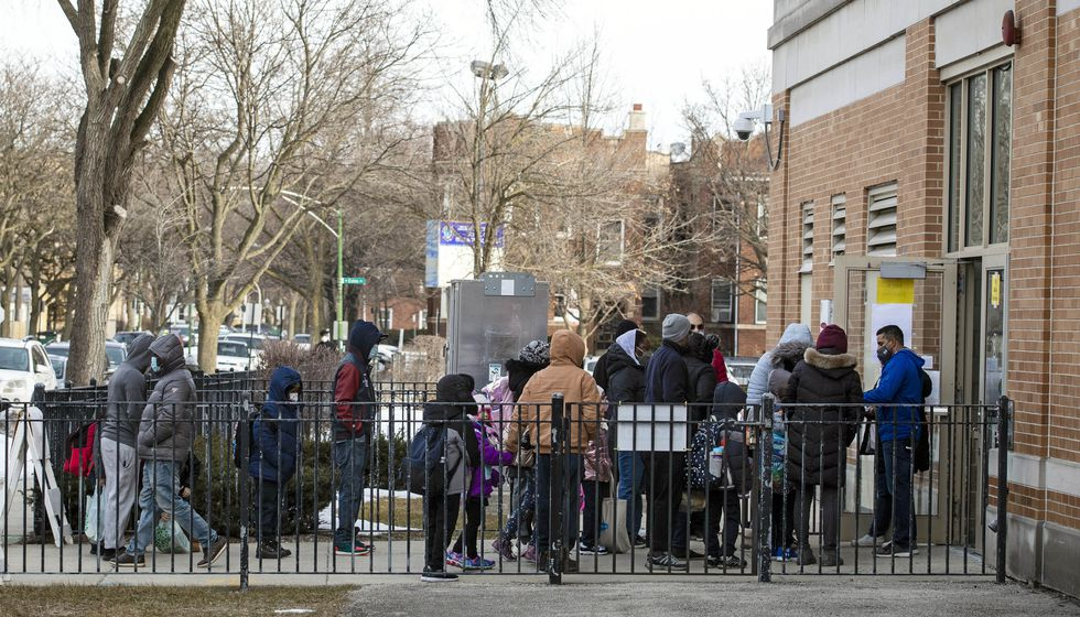 FILE - In this March 1, 2021 file photo, parents and children line up outside George B....