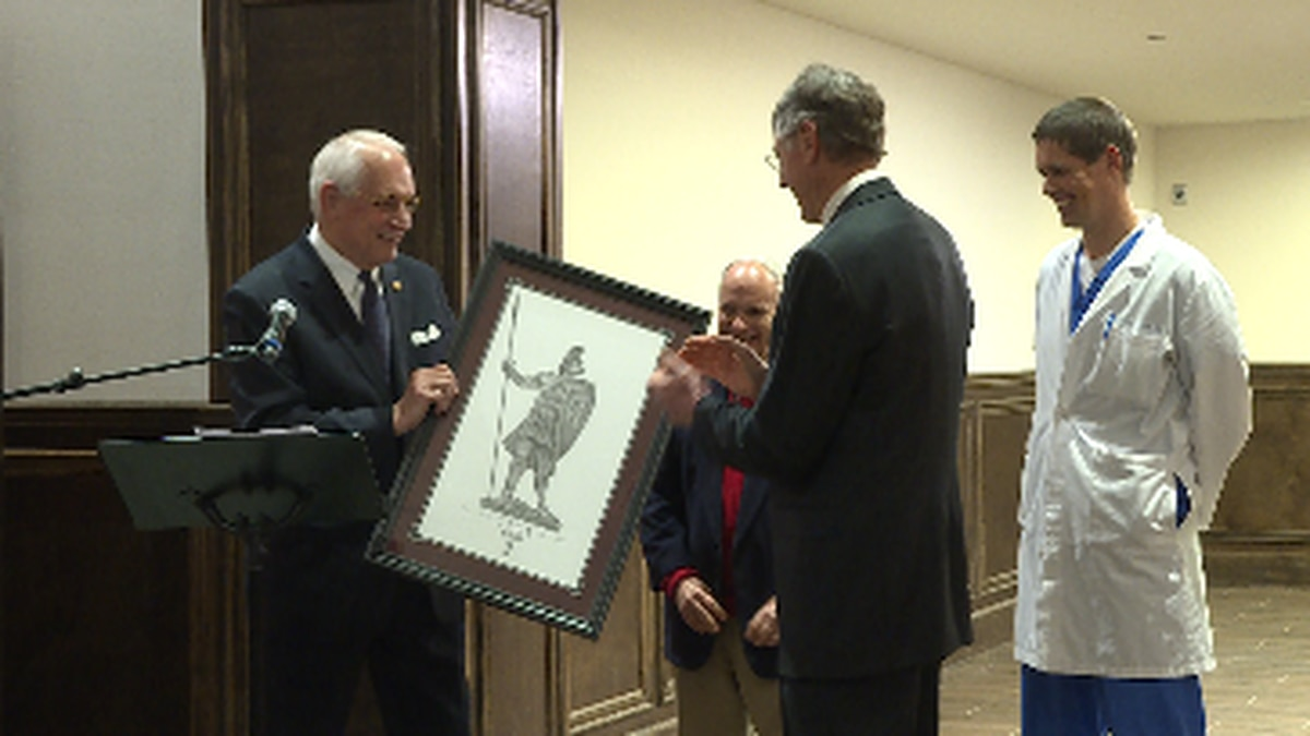 Dr. Jack Hawkins Jr. presents donor Dr. Marnix Heersink with a gift for his generous donation