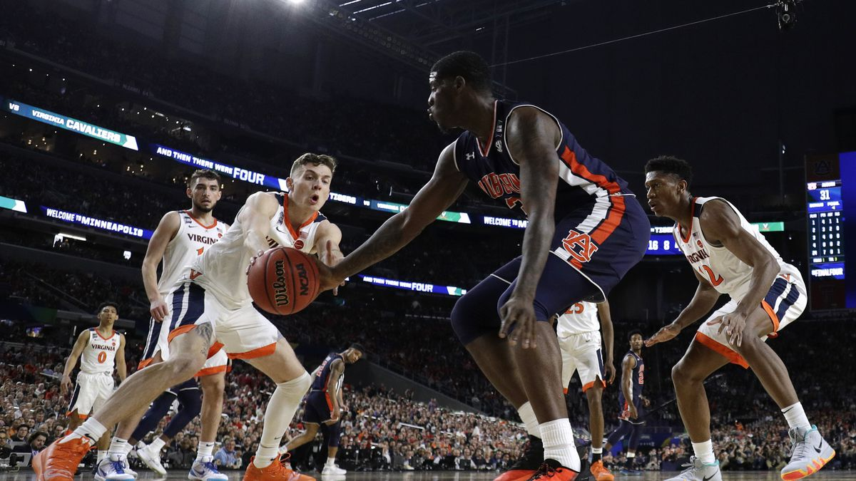 Virginia guard Kyle Guy, left, fights for a loose ball with Auburn forward Danjel Purifoy...