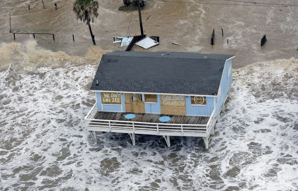 FILE - In this Sept. 12, 2008, file photo, a boarded-up home sits along the beach as Hurricane...