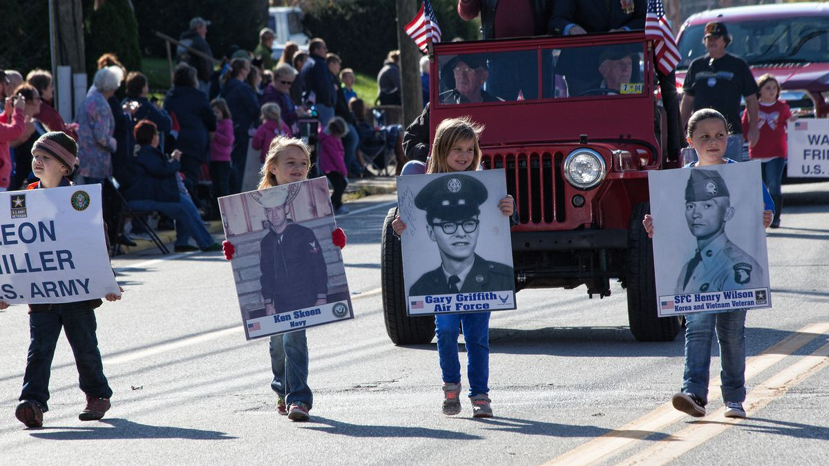 (File Photo) Local children carry the posters of family members in the Military Honor March of...