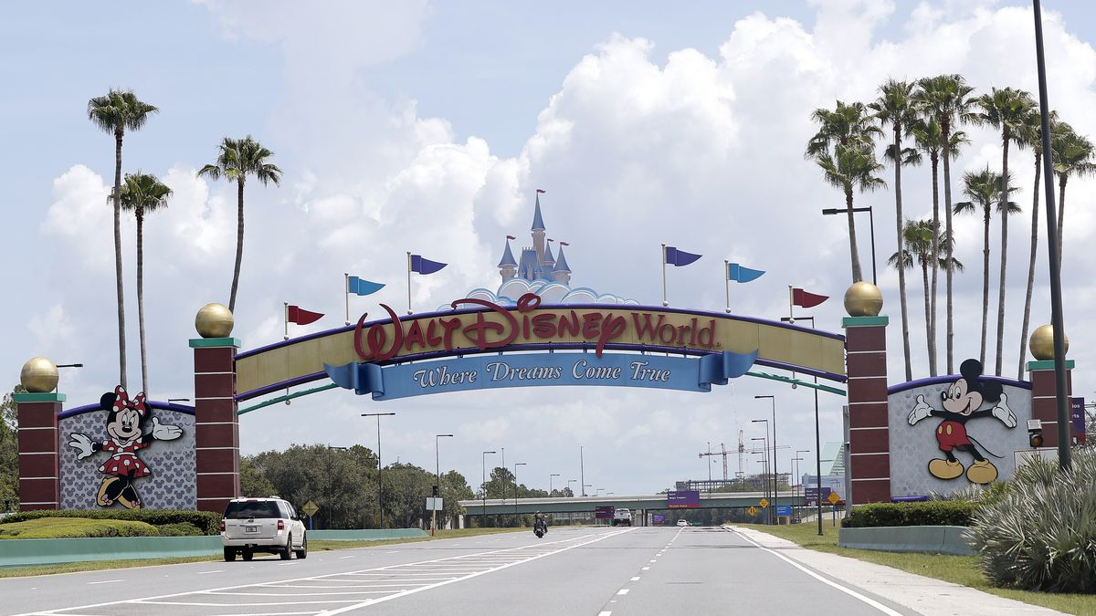 Cars drive under a sign greeting visitors near the entrance to Walt Disney World, Thursday, July 2, 2020, in Lake Buena Vista, Fla.