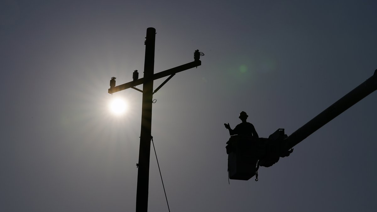 In the aftermath of Hurricane Ida, a lineman gestures as he works on a power pole, Sunday,...