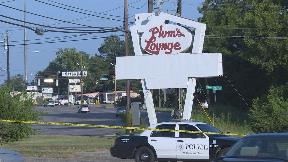 A Dothan police car sits under the sign at Plum's Lounge where a man was shot to death in July...