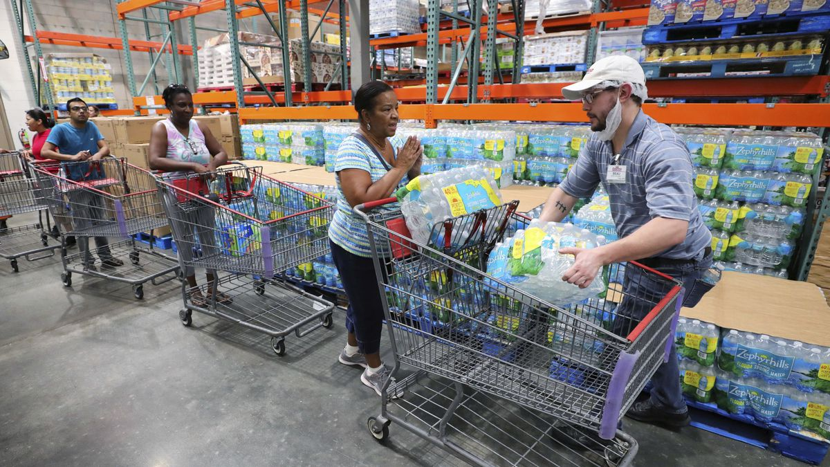 A shopper is grateful to get two cases of bottled water —the limit per customer — at a Costco store in Altamonte Springs, Fla., Friday, Aug. 30, 2019, as central Florida residents prepare for a possible strike by Hurricane Dorian. (Joe Burbank/Orlando Sentinel via AP)
