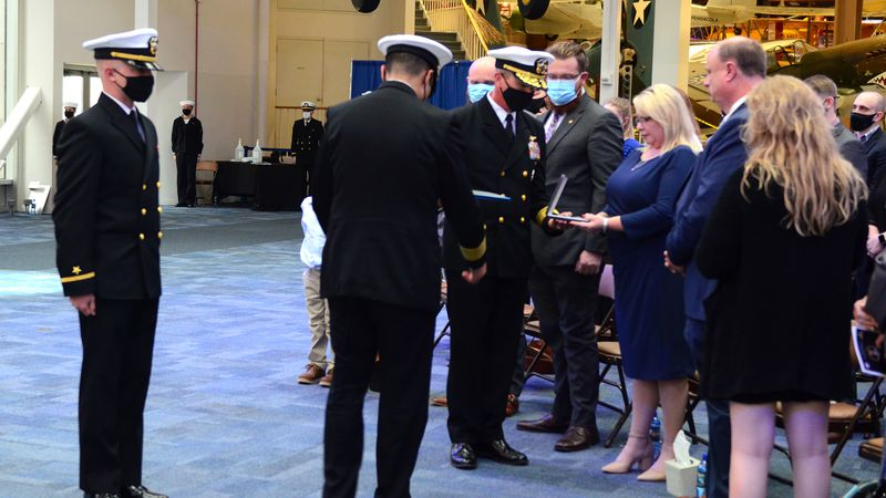 The family of Ensign Joshua Watson is presented a Purple Heart Medal posthumously by Rear Adm....
