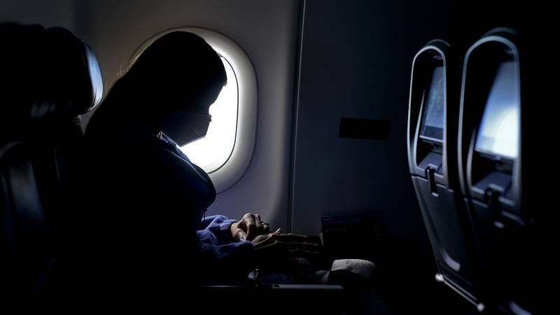 FILE - In this Wednesday, Feb. 3, 2021, file photo, a passenger wears a face mask she travels...