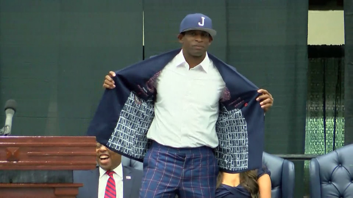 Deion Sanders opens his jacket to show it lined with the JSU logo.  Jackson State University introduced the NFL Hall of Famer as their new head football coach Monday morning.