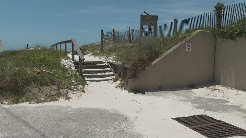 There are no signs indicating what beach warning flags mean at one beach access in Miramar beach.