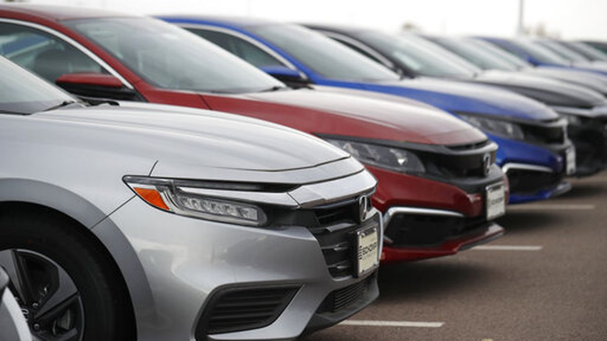 In this Sunday, Oct. 20, 2019, photograph, a long row of unsold 2020 Civic sedans at a Honda dealership in Littleton, Colo. (AP Photo/David Zalubowski)
